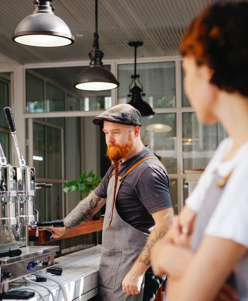 Masculine barista with crop partner at work in coffee house