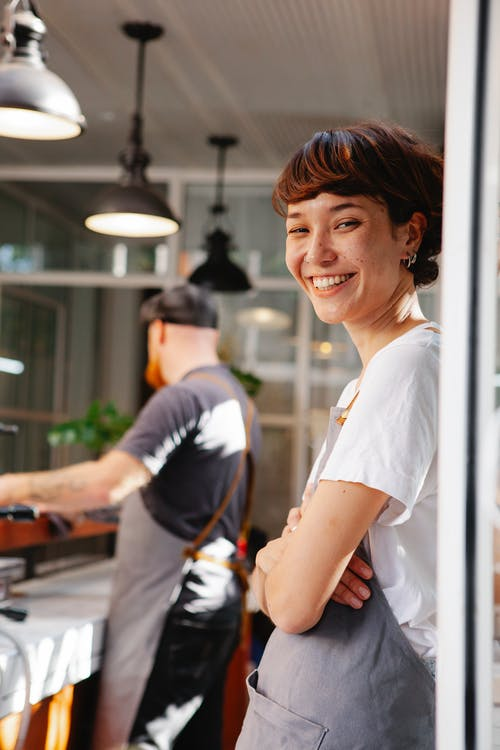 Smiling barista with unrecognizable partner in cafeteria kitchen