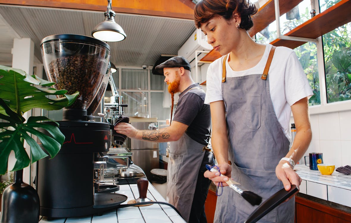 Crop baristas against coffee maker and grinder in cafe kitchen