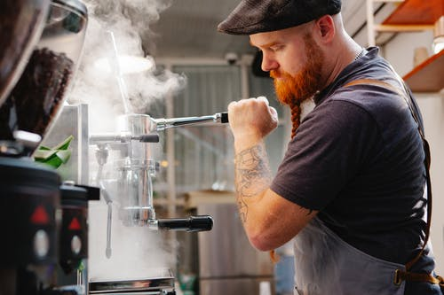 Crop employee cleaning espresso maker with vapor at work