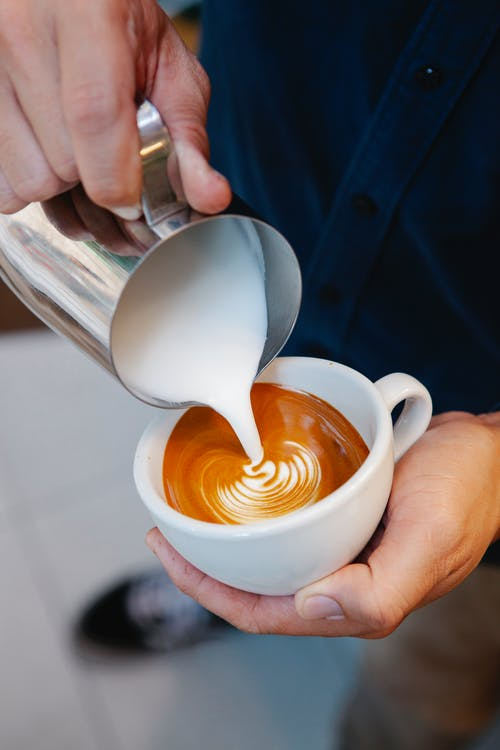 From above of crop unrecognizable male employee pouring milk from jug into tasty coffee with froth in cafe