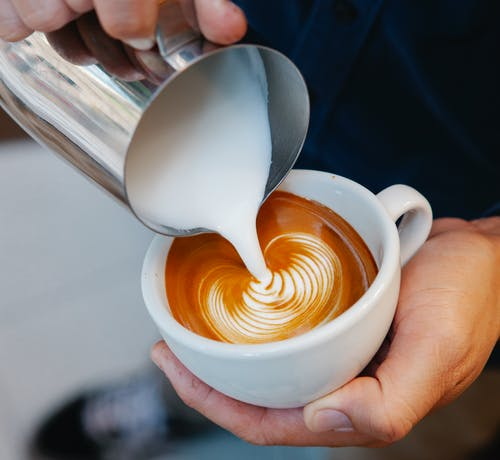 Crop unrecognizable male cafe worker pouring fresh milk from pitcher into aromatic coffee with foam