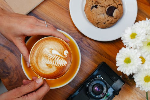 Crop woman with delicious latte near cookie and photo camera