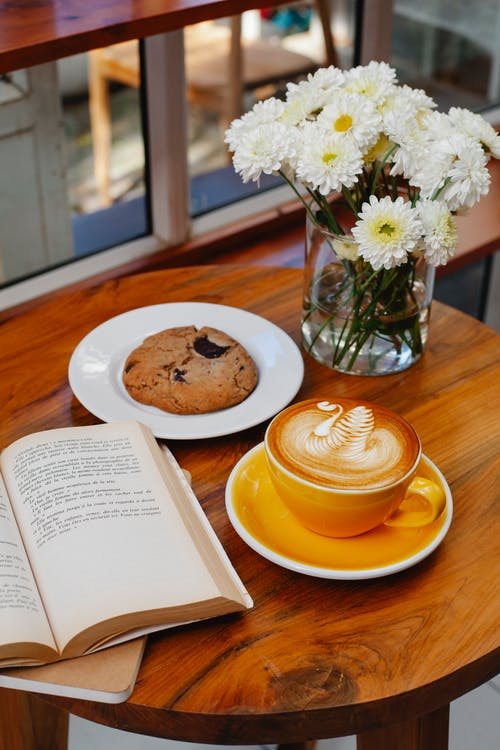 From above of tasty coffee with ornament on froth near biscuit and open book on cafeteria table
