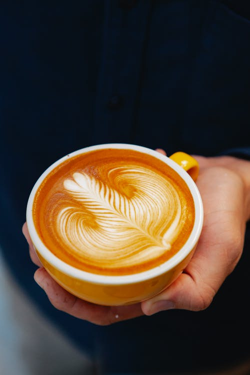 Crop barista showing cup of tasty latte with ornament