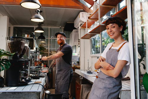 Cheerful young baristas in aprons working together in contemporary cafeteria kitchen and looking at camera with smiles