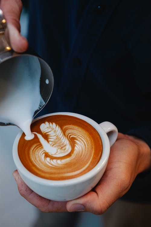 Crop faceless barista adding froth into cup of latte