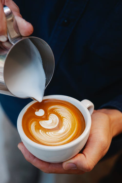 High angle crop unrecognizable male barista adding fresh frothy milk from pitcher into cup of latte and making latte art
