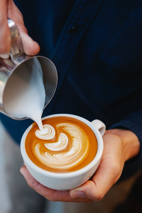 Man preparing aromatic coffee and making latte art