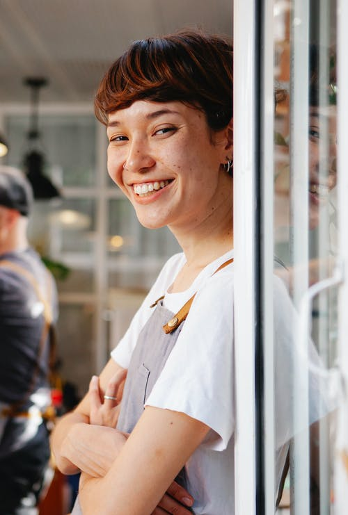 Happy young woman in apron smiling at camera