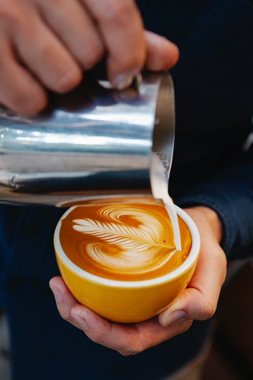 Man pouring cream into coffee with latte art
