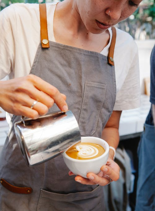 Crop female in apron preparing cup of coffee with latte art and warm milk in cafe