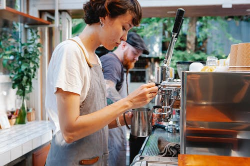 Young woman in apron using coffee machine