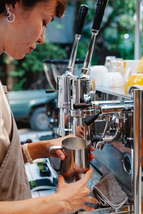Woman using coffee machine and metal pitcher
