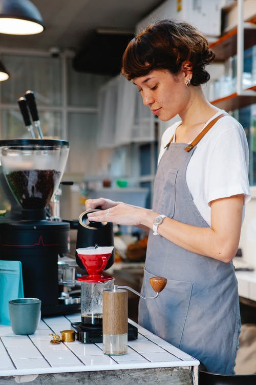 Side view of female barista in apron pouring water into coffee dripping through paper filter in cafe