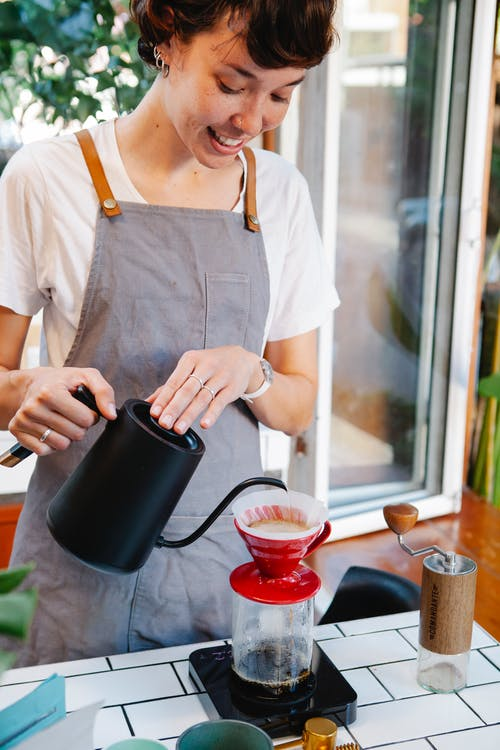 Crop cheerful female barista in casual clothes and apron brewing fresh coffee with filter dripper in light kitchen in cafe in daytime