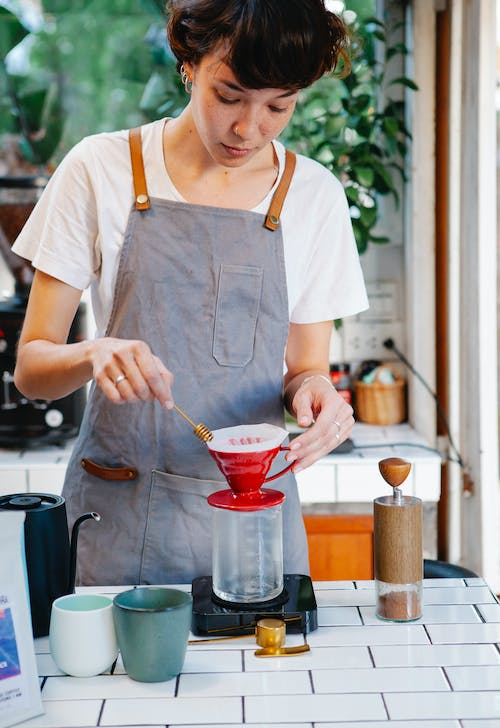 Crop woman barista in gray apron making pour over coffee with hot water in light cafe in daytime