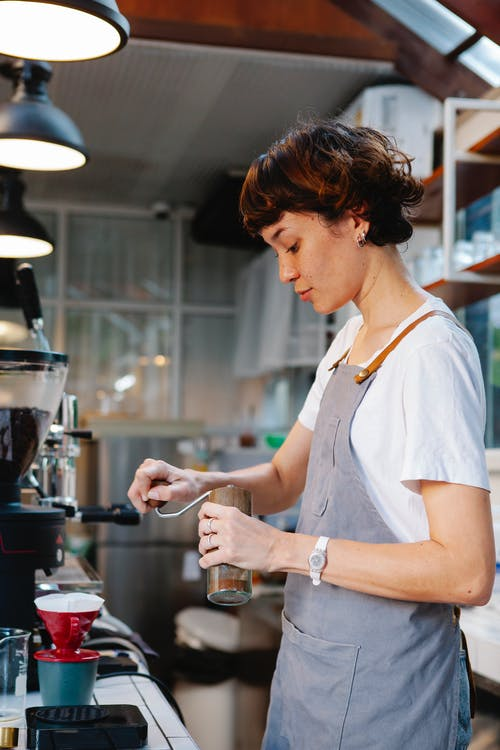 Focused woman barista in gray apron standing and grinding coffee beans with manual stainless steel grinder for pour over coffee in cafe