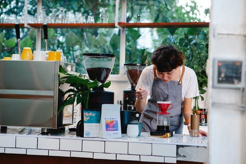 Thoughtful female barista with brown hair in apron pouring aromatic alternative coffee while working in light cafe in daytime