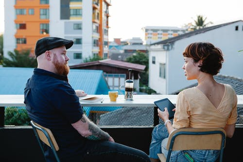 Back view of young woman with tablet and stylish man resting with cup of coffee in terrace in daytime