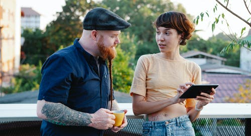 Young man with beard in cap and woman using tablet speaking on terrace in daytime in summer
