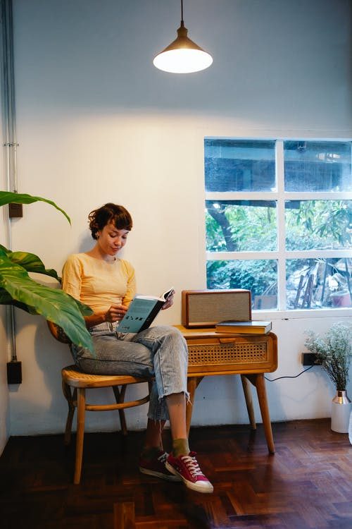 Young woman reading book on chair under bright lamp