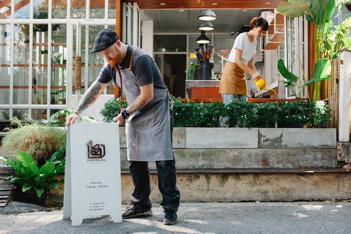 Man in cap and apron installing signboard on street while woman watering verdant plants in cafe