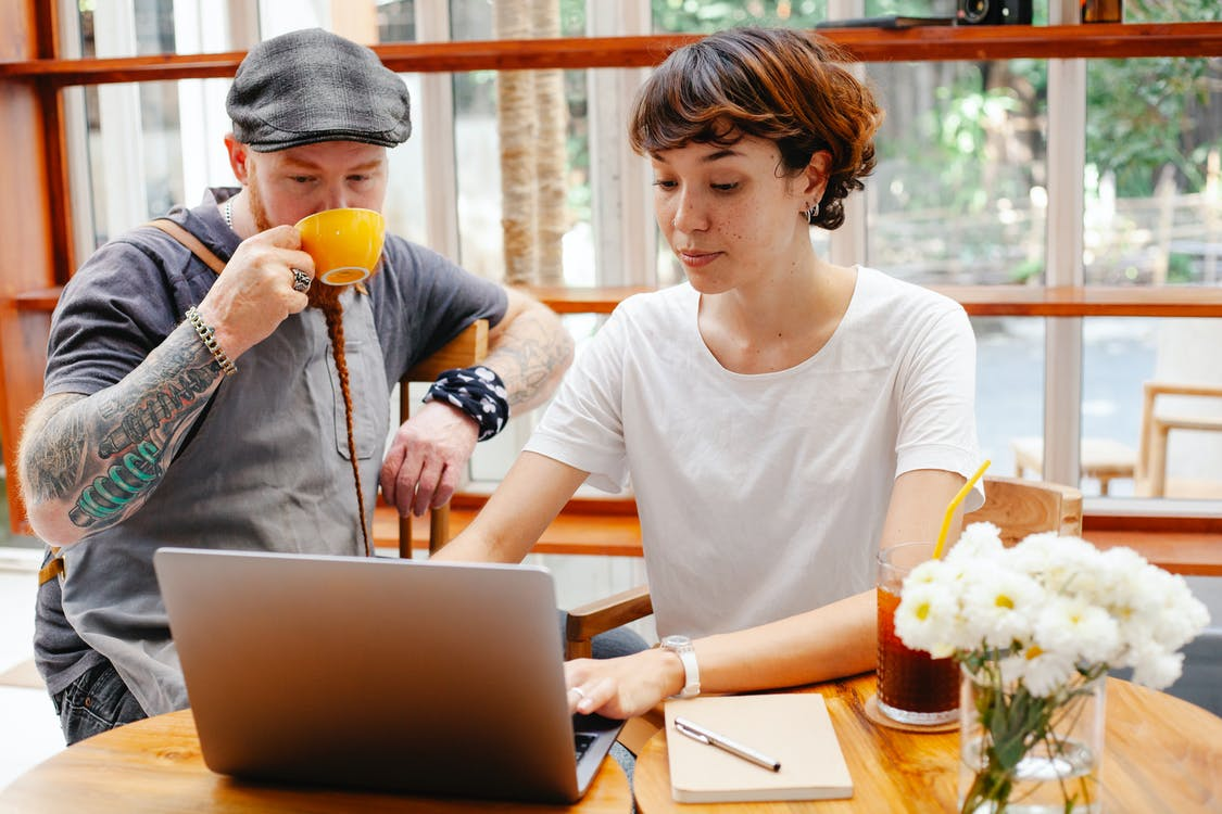 Pensive young woman typing on netbook while man with cup drinking coffee at table of cafe