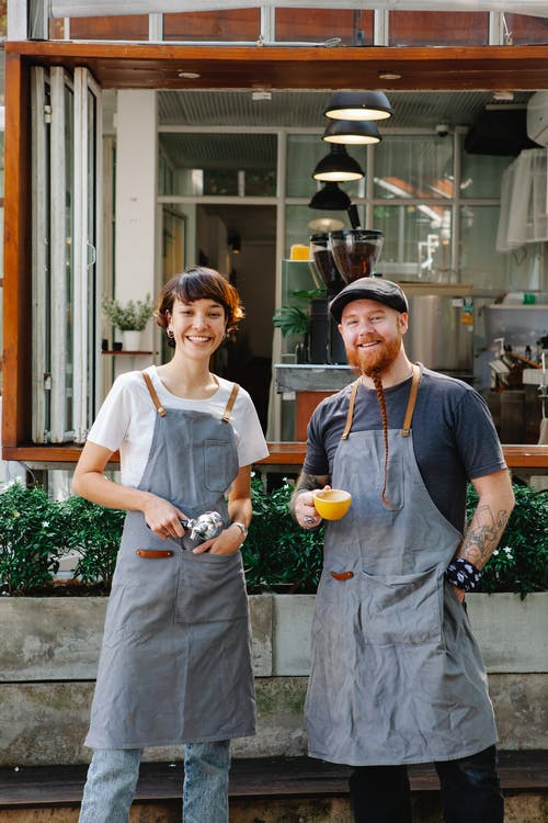 Positive man with cup of coffee and woman with filter holder standing on terrace of modern cafe during work break