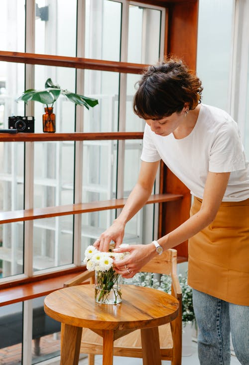 Serious female in apron arranging white flowers in glass vase on wooden table while working in cafe near big window