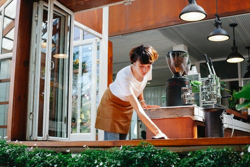 From below of focused female in apron cleaning wooden counter of modern coffee house with coffee makers and special equipment