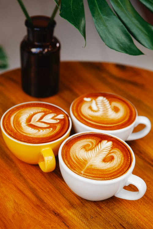 Cups of latte on wooden table