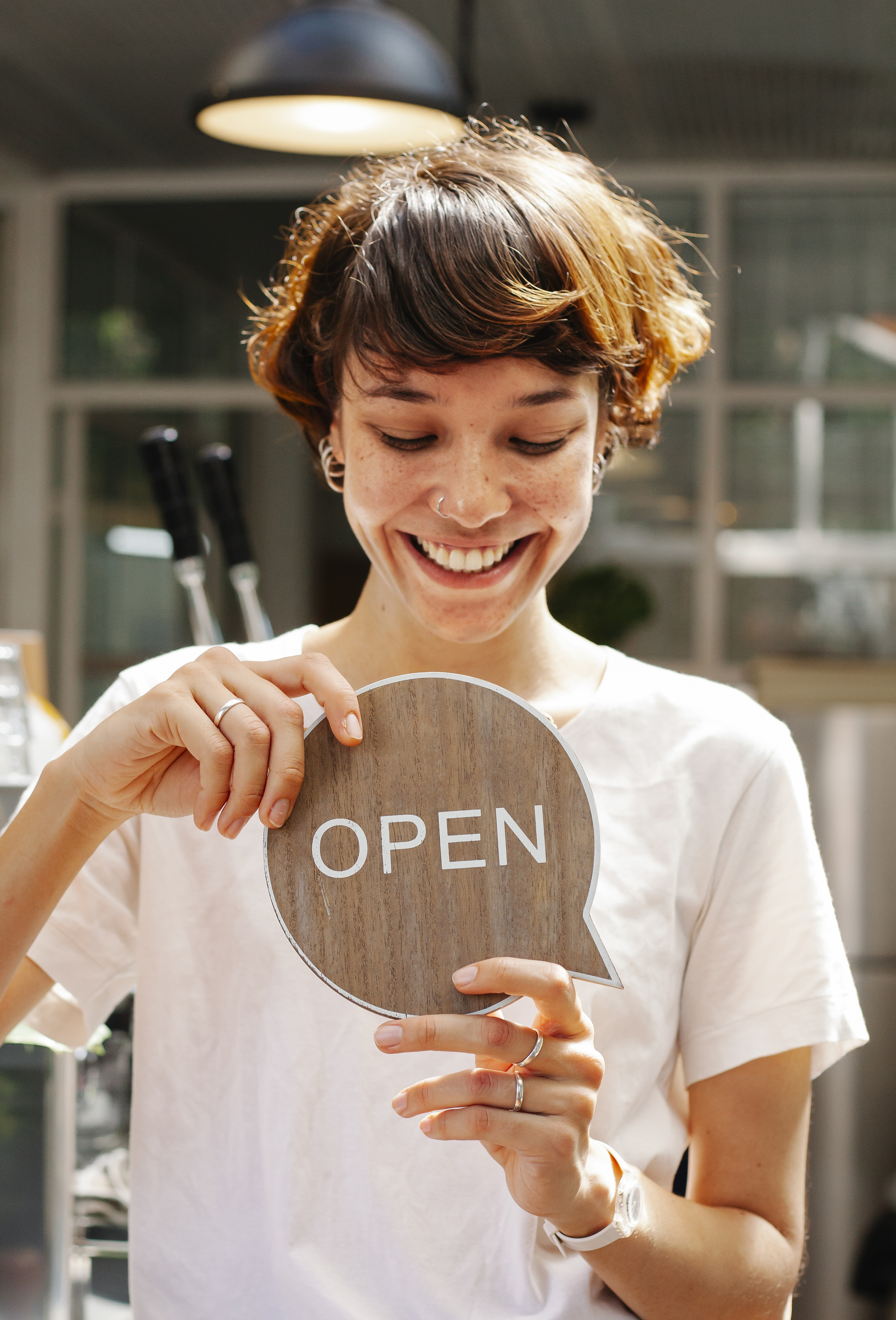 through window of cheerful woman with sign open in cafe