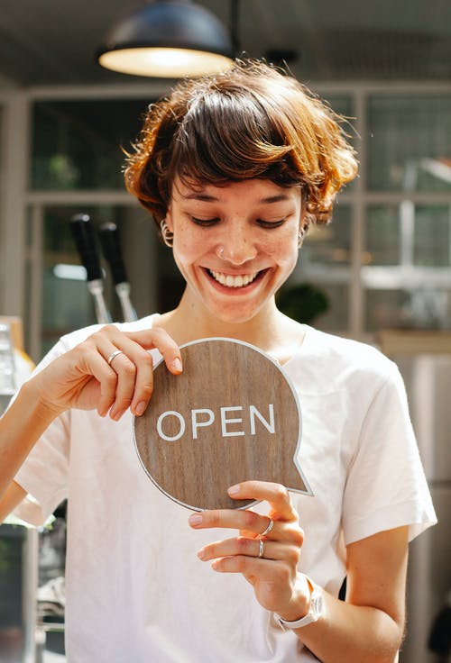 Through glass of happy female worker holding wooden Open sign working in modern cafe with glowing lamp inside