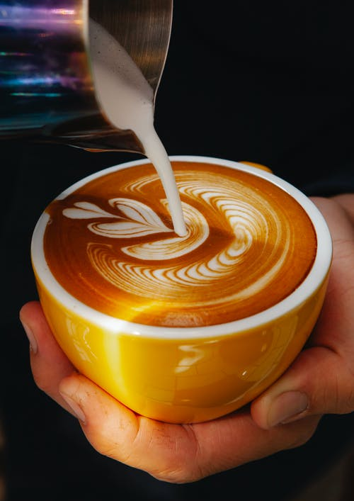 Unrecognizable professional male barista with mug of coffee making latte art with leaf pattern in modern coffee house during work