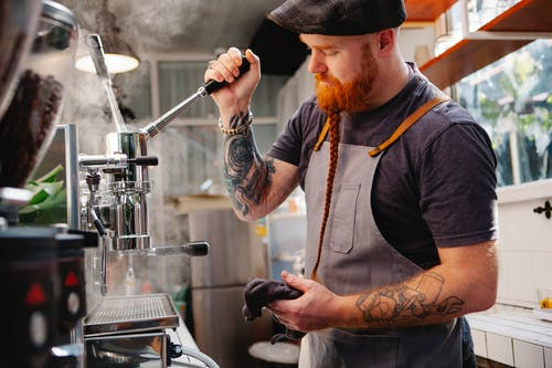 Side view of tattooed male with beard wearing cap standing near coffeemaker with lever and steam while working in coffee house