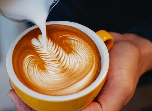 Crop barista making latte art