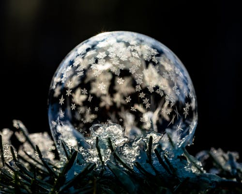 Transparent frozen sphere with ice on cold ground with hoarfrost on black background