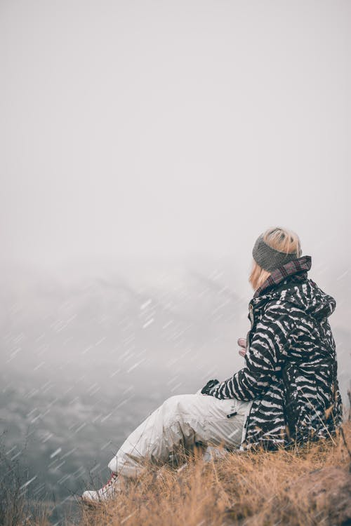 Person in Black and Gray Jacket Sitting on White Snow Covered Ground