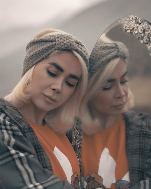 Woman in Gray Knit Cap Beside Woman in Orange Shirt