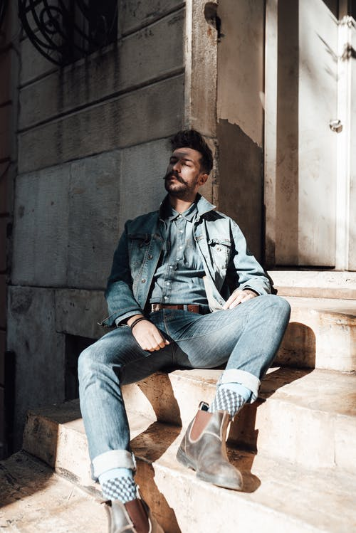 Contemplative adult male in trendy denim wear resting with eyes closed on stone stairs on sunny terrace