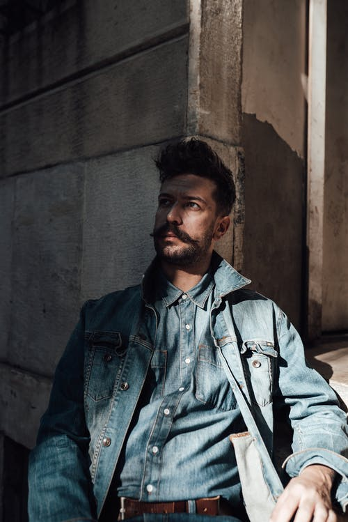 Contemplative adult male with mustache and beard wearing denim jacket sitting outside stone building and looking away in deep thoughts
