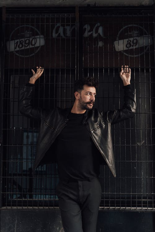 Confident stylish male with mustache wearing black leather jacket standing with arms raised against grid wall and looking away