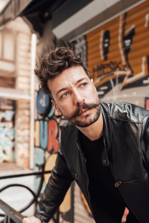 Pondering adult male with mustache and beard in leather jacket standing on street with graffiti on wall and looking away in thoughts