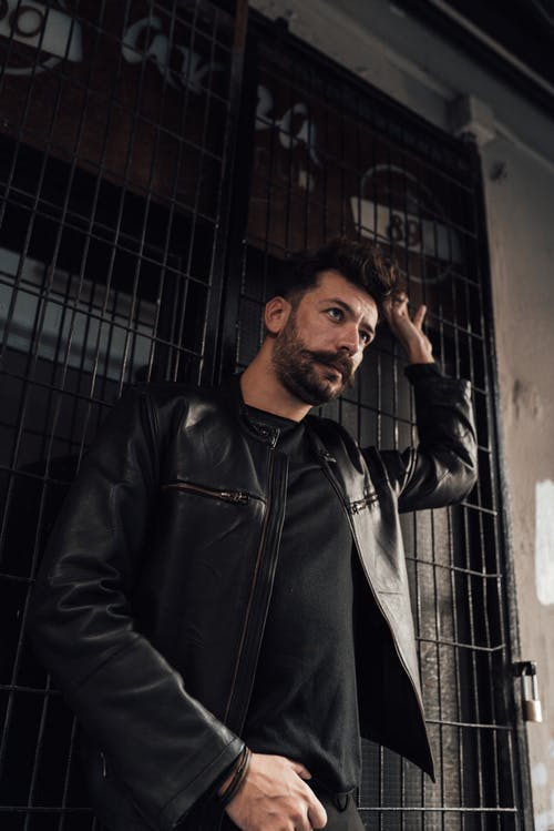 Confident serious male with mustache and beard standing with arm raised against grid wall and looking away pensively