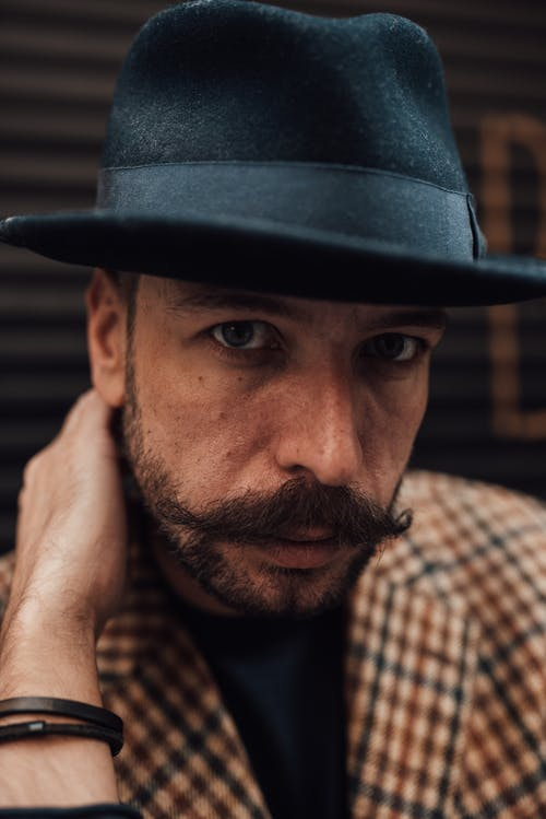 Confident well dressed man in hat touching neck