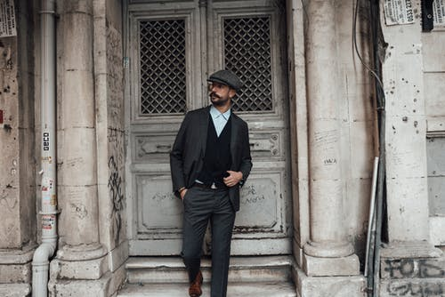 Confident male with beard and mustache in stylish formal clothes standing with hand in pocket against old stone building in daytime
