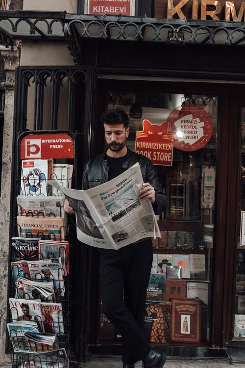 Pensive man in stylish clothes reading newspaper on street