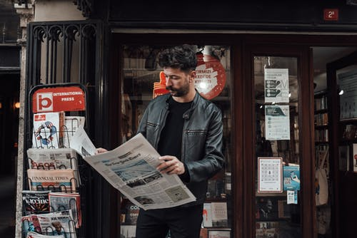 Serious bearded male with trendy haircut in casual clothes reading newspaper while standing near entrance of shop