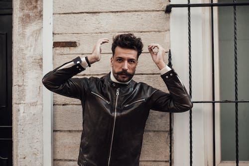Confident stylish man with hands near head